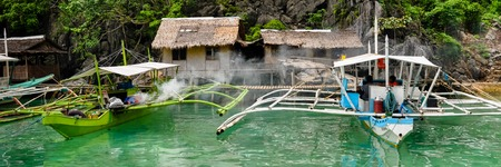 coron: Two wooden Boats in Front of Nipa wood house on stilts at the sea near Coron, Palawan, Philippines Stock Photo