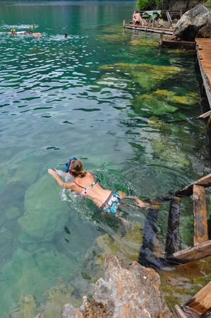 clear path: Woman swimming in very Clean and Clear lagoon lake water next to a wooden path near Coron, Palawan, Philippines