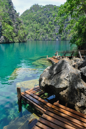 coron: Very Clean and Clear lagoon lake Water next to a wooden path near Coron, Palawan, Philippines