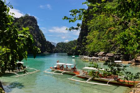 coron: Traditional wooden filipino boats in a blue lagoon at tropical island near Coron, Palawan, Philippines