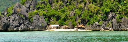 coron: Rocky Island With Nipa Huts on a lonely White Sand beach near Coron, Palawan, Philippines