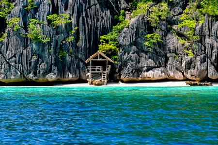 coron: Lonely wooden bamboo hous on stilts at a small hidden beach on rocky island near Coron, Palawan, Philippines