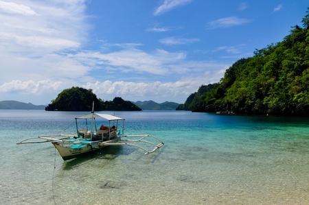 blue lagoon: Barca tradizionale filippino di legno in una laguna blu con acqua cristallina a isola tropicale nei pressi di Coron, Palawan, Filippine