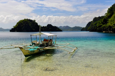 coron: Traditional wooden filipino boat in a blue lagoon with crystal clear water at tropical island near Coron, Palawan, Philippines Stock Photo