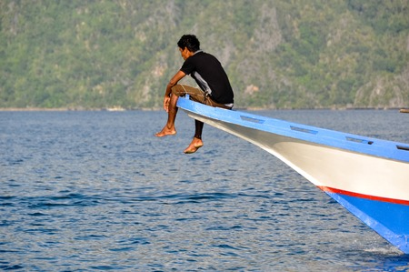 coron: Man Sitting in the front of a wooden boat near Coron, Palawan, Philippines Stock Photo