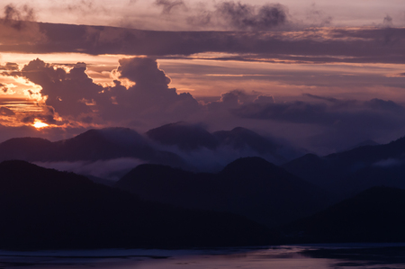 coron: Silhouette of Mountains Above the Water under purple cloudscape clouds  at sunset near Coron, Palawan, Philippines