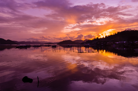 coron: Pretty Pink orange Sky cloudscape over an island with reflection at Sunset on the Island of Coron, Palawan, Philippines Stock Photo