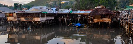 coron: Small nipa homes all jammed together and built on the black water in Coron Stock Photo