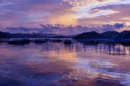 coron: Pretty Pink orange Sky cloudscape over an island with reflection and wooden traditional filipino boats at Sunset on the Island of Coron, Palawan, Philippines Stock Photo