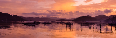 billow: Pretty Pink orange Sky cloudscape over an island with reflection and wooden traditional filipino boats at Sunset on the Island of Coron, Palawan, Philippines Stock Photo