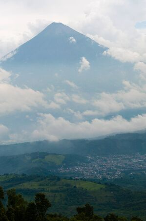 billow: Big Summit of volcano Surrounded By Fog and Clouds over green field near Antigua, Guatemala
