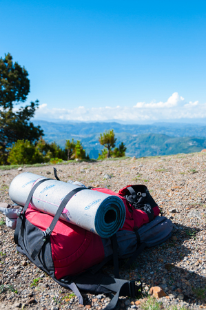 lays: Red Backpack With sleeping mat Lays on rocky ground in front mountain Tajamulco and blue sky with clouds in Guatemala Stock Photo