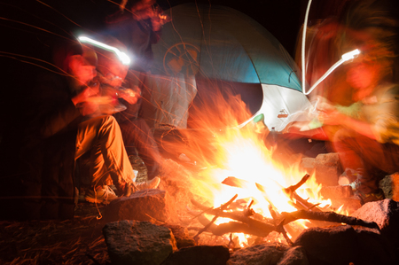 gathered: Hikers Gathered Around a campfire at night with long exposure shot in the mountain Tajamulco in Guatemala Stock Photo