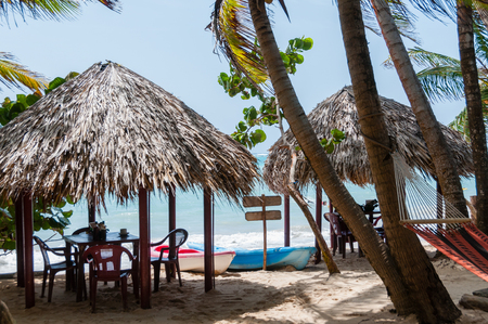 corn island: Two Huts With Tables Chairs and Hammock at the white sand beach in front of caribbean sea on Corn Island in Nicaragua Stock Photo