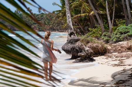 corn island: Beautiful Blond Woman with pink bag walking barefoot along the lonely caribbean white sand beach and coconut palm trees on little corn island in Nicaragua