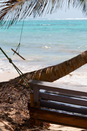 corn island: Wooden Bench Swing next to a palm tree in front of the caribbean white sand beach ocean on little corn island in Nicaragua Stock Photo
