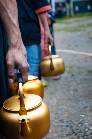 golden pot: People of Sulawesi in Queue with golden pot in hand, during a funeral in Tana Toraja, Sulawesia, Indonesia Stock Photo