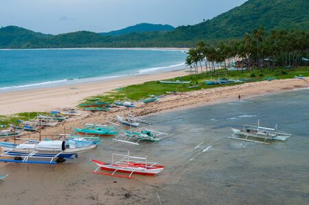 nido: Boats and palm trees at the sand beach in front of ocean, close to El Nido, Palawan, Philippines Stock Photo