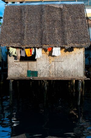 coron: Small nipa homes with clothes hanging outsied on the water in Coron