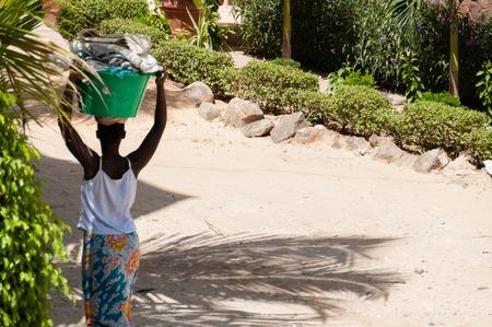 African woman carrying bucket on her head in dust street of Dakar, Senegal