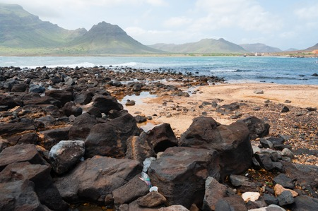 Black rock stone sand beach coast in front of blue sea with mountain background on Cape Verde island Stock Photo