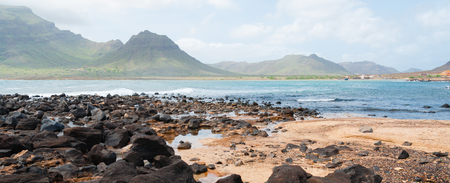 santiago cape verde: Black rock stone sand beach coast in front of blue sea with mountain background on Cape Verde island Stock Photo