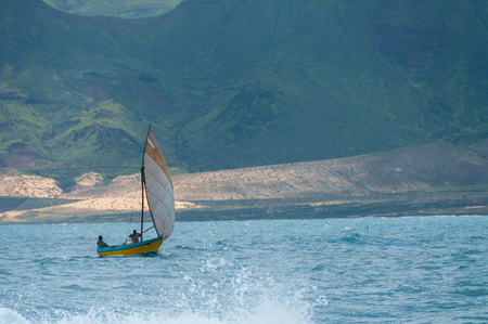 Small wooden fisherman sail boat with two men in the blue windy ocean front of a mountain on Cape Verde island