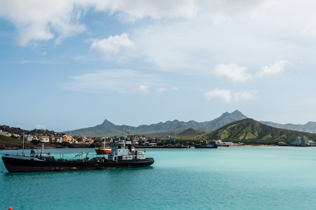Ship in front of small town at the blue ocean coast with cloudy mountain background, Cape Verde island off the coast of africa