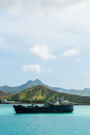 Old rusty Ship in the blue ocean at coast with cloud and green mountain background, Cape Verde island off the coast of africa