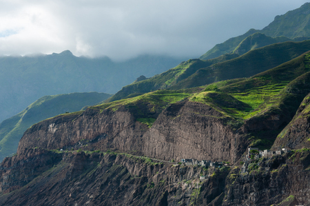 santiago cape verde: Cloud black rock stone coastline with houses and green hill in cape verde island close to africa Stock Photo