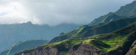Cloud black rock stone coastline with houses and green hill in cape verde island close to africa