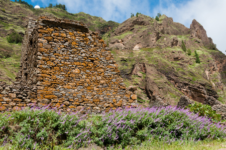 Stone house and lavender at foot of rocky mountain on a pathway in cape verde island Stock Photo