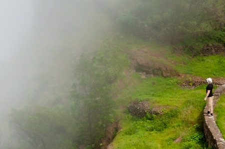 White man with black shirt and hat standing on misty fog cliff on cape verde island