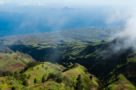 Steep green valley viewpoint leading to blue ocean coast of cape verde island off the coast of africa Stock Photo