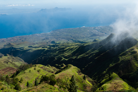 island: Steep green valley viewpoint leading to blue ocean coast of cape verde island off the coast of africa Stock Photo