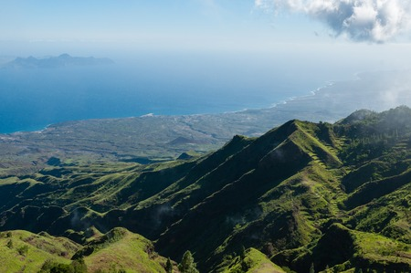 Steep green valley viewpoint leading to blue ocean coast of cape verde island close to the coast of africa Stock Photo