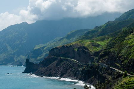 Black coastline road with houses on green cape verde island with high mountains and clouds