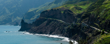 island: Black coastline road with houses on green cape verde island with high mountains and clouds