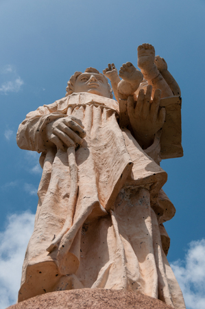 santiago cape verde: Religious statue of a man holding a child in his hand on top of a viewpoint on cape verde island Stock Photo