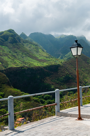 barrier island: Lantern in front of barrier and green valley or mountain in cape verde island Stock Photo