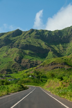 Asphalt road leading in fresh green mountain with clouds on top of cape verde island