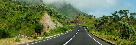 santiago cape verde: Asphalt road leading in fresh green mountain with clouds on top of cape verde island Stock Photo