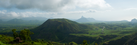 Green valley with hill in the middle under cloudy sky on Cape Verde island Stock Photo