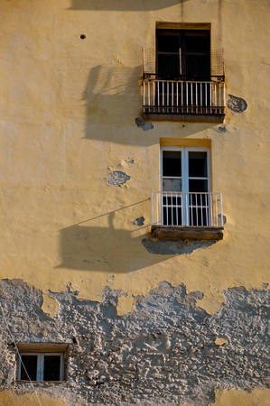 balcony window: Old Italian yellow stone house front with balcony and window in city of Tropea, Calabria, Italy