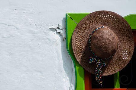 doorway: Brown straw hat hanging on colorful doorway in Salento, Colombia