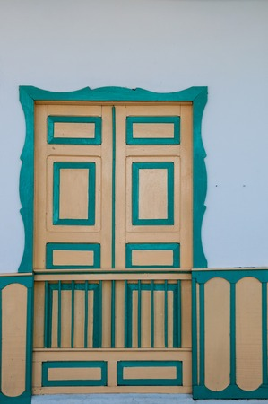 colonial house: Yellow turquoise wooden door of a colonial house front in Salento, Colombia, South America Stock Photo