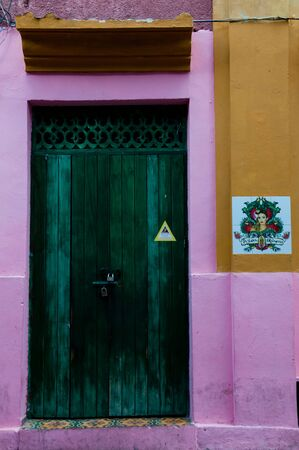 colonial house: Green wooden door of a pink yellow colonial house front Cartagena, Colombia, South America