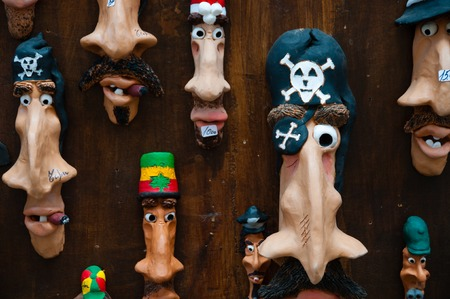 elongated: Funny handmade elongated faces art on wood wall in a shop in Tropea, calabria, italy
