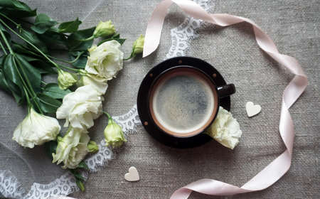 A cup of coffee and a bouquet of white roses Stock Photo