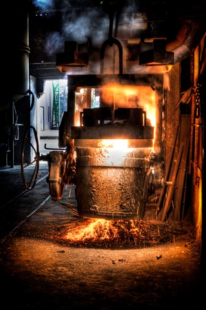 ferrous foundry: Ladle of molten steel in a iron foundry Stock Photo